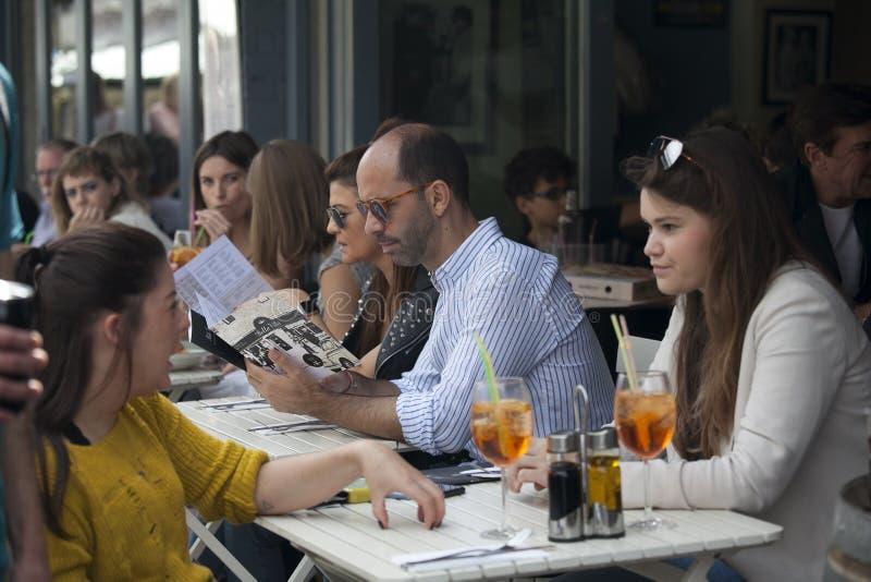 Os homens e as mulheres leram o menu em um café da rua perto do mercado da estrada de Broadway fotografia de stock