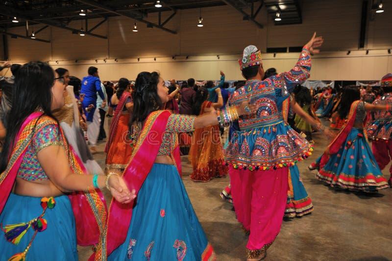 Os homens e as mulheres são de dança e apreciando o festival hindu de vestir de Navratri Garba tradicional consuma imagens de stock royalty free