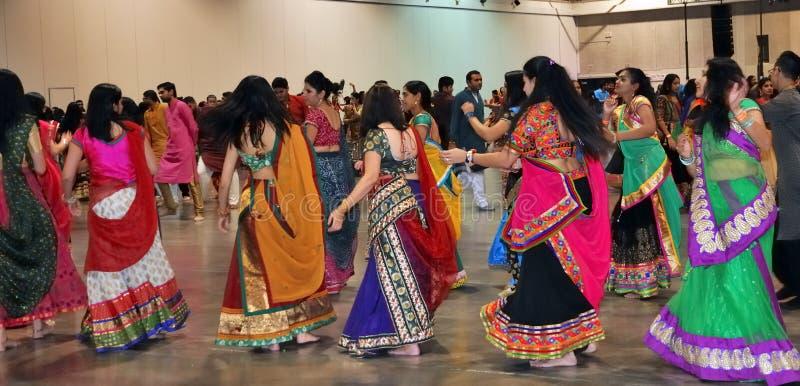 Os homens e as mulheres são de dança e apreciando o festival hindu de vestir de Navratri Garba tradicional consuma foto de stock