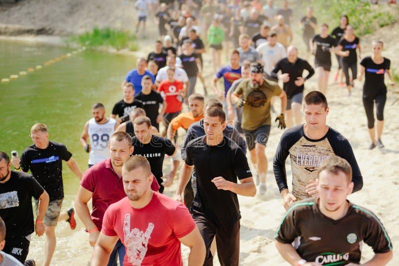 Os homens e as mulheres superaram no início a barreira aquosa da lama durante a raça à legião foto de stock