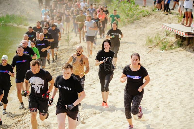 Os homens e as mulheres superaram no início a barreira aquosa da lama durante a raça à legião fotografia de stock royalty free