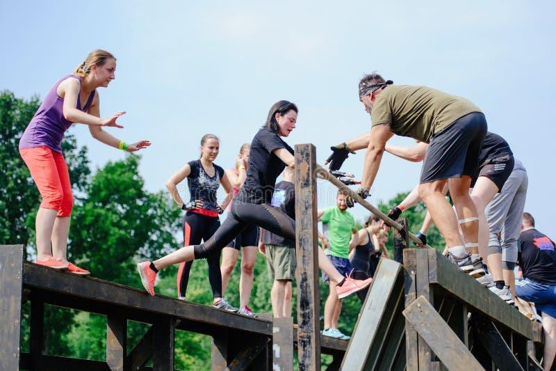 Os homens e as mulheres superaram no início a barreira durante a raça à legião foto de stock royalty free