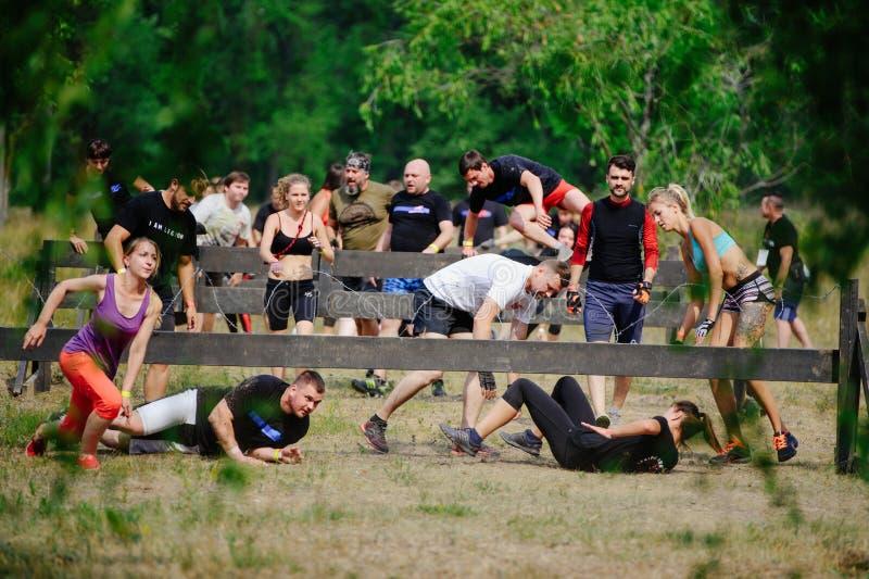 Os homens e as mulheres superaram no início a picada farpada durante a raça à legião fotografia de stock royalty free