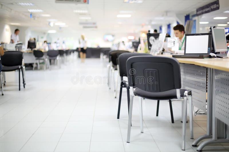 Os homens e as mulheres trabalham em computadores no escritório do concessionário automóvel foto de stock