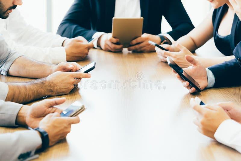 Os homens e a mulher de negócio estão usando o telefone na mesa dentro do espaço de escritórios imagem de stock royalty free