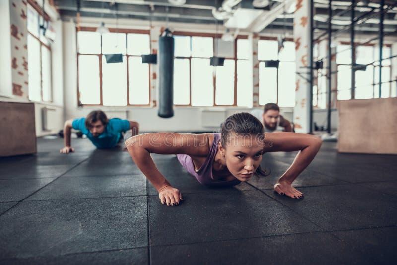 Os homens e a mulher que fazer empurra levantam no Gym brilhante foto de stock royalty free