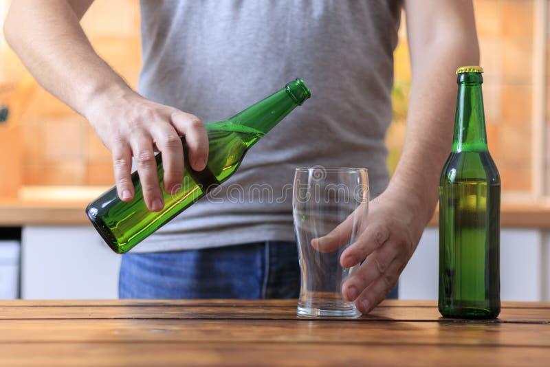 Os homens estão derramando a cerveja da garrafa verde ao vidro imagem de stock