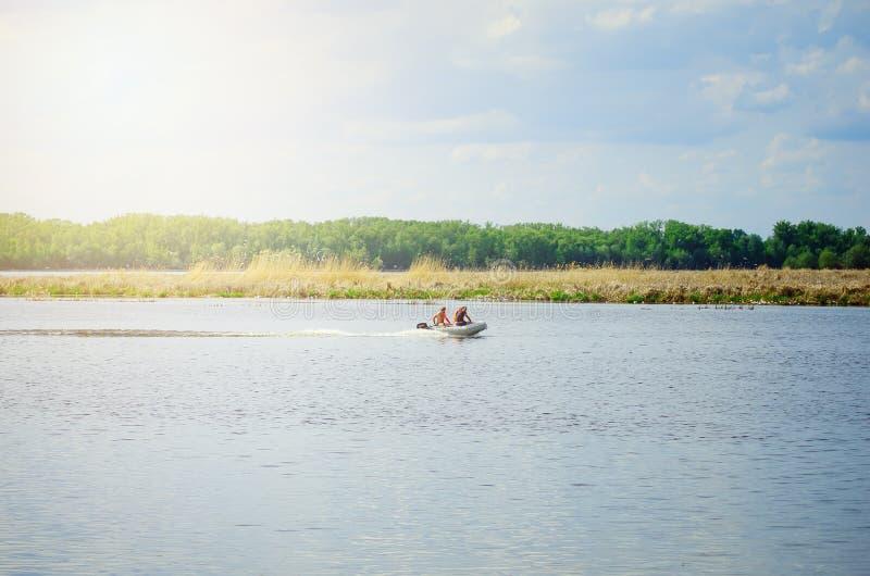 Os homens estão nadando em um barco de motor inflável no rio imagens de stock