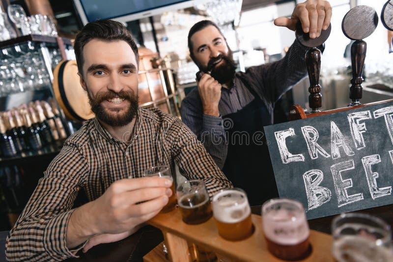 Os homens farpados felizes testam a cerveja de estilos diferentes em demonstradores da cerveja na cervejaria da cerveja do ofício imagens de stock royalty free
