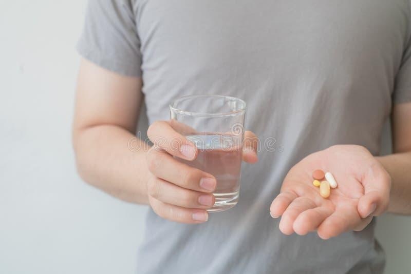 Os homens guardam a medicina e a água em suas mãos Conceitos médicos e da saúde imagem de stock royalty free