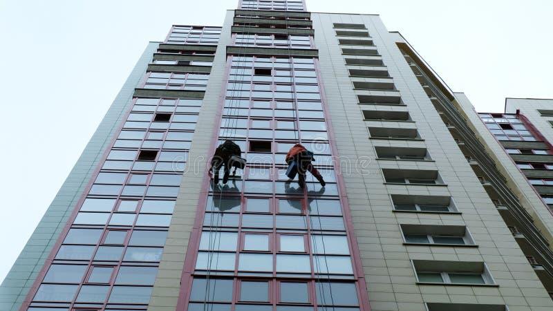 Os homens lavam janelas, lavam janelas em um arranha-céus, trabalho como um montanhista imagem de stock