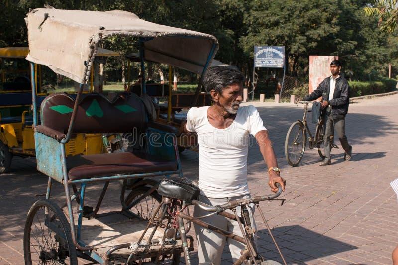 Os homens não identificados conduzem o pedicab na frente do calibre ocidental de Taj Mahal o monumento do amor imagens de stock royalty free
