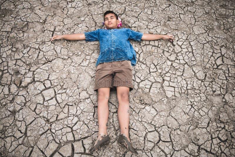 Os homens na terra racharam seco devido à seca imagens de stock