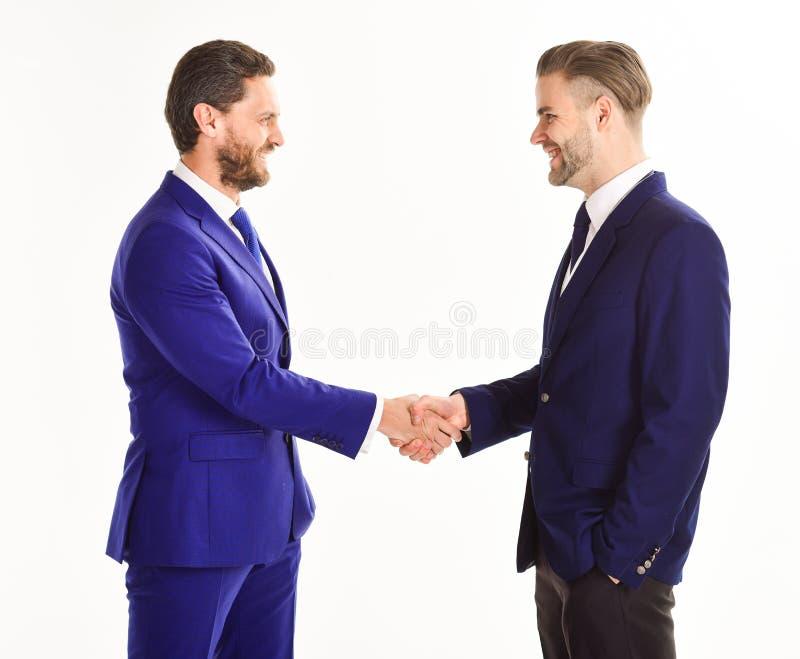 Os homens nos ternos ou nos homens de negócios guardam as mãos no aperto de mão imagens de stock