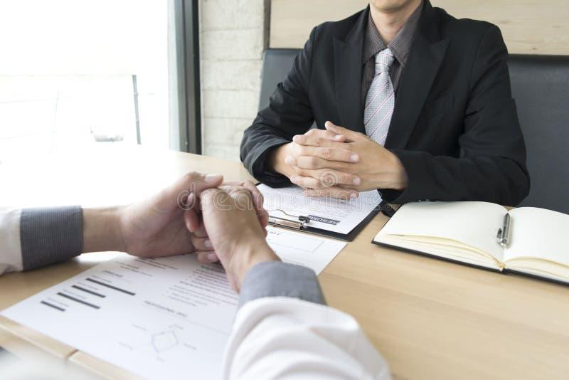 Os homens novos estão sendo entrevistados por empregadores O empregador veste um terno preto que explica a candidatura a cargo imagem de stock