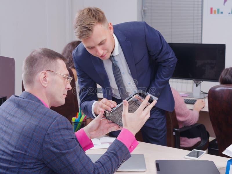 Os homens novos no escritório estão olhando a placa de vídeo fotografia de stock