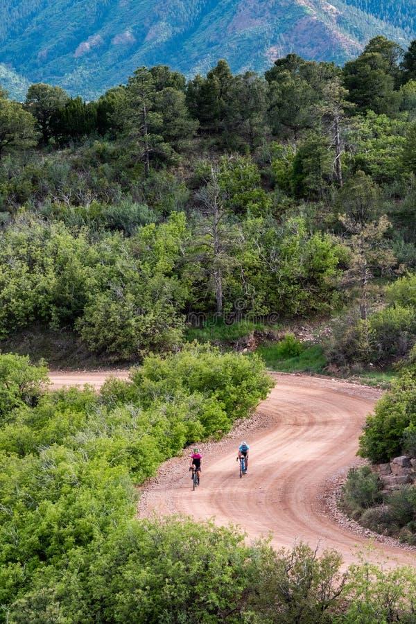 Os homens que biclying em piques da estrada da montanha da sujeira repicam a cordilheira Colorado Springs imagens de stock