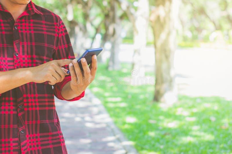 Os homens que vestem camisas listradas vermelhas usam telefones celulares no parque fotos de stock royalty free