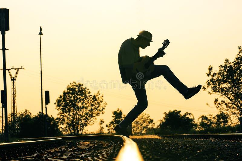 Os homens são jumpig na trilha com a guitarra no meio do ar fotografia de stock royalty free