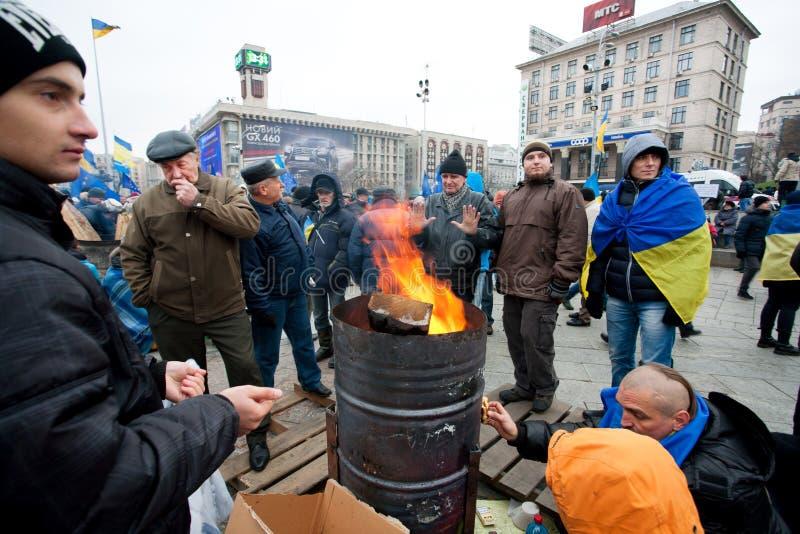 Os homens sérios na rua fria que ocupa Maidan principal esquadram e exigem o governo assinar os originais da adesão à UE fotos de stock royalty free