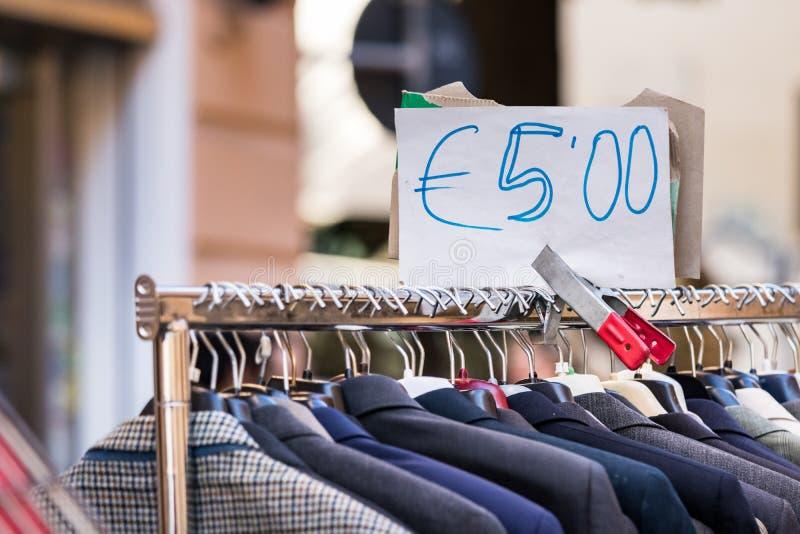Os homens serem a segunda mão em uma cremalheira para a venda a preço barato em um mercado de rua em Ancona Itália foto de stock