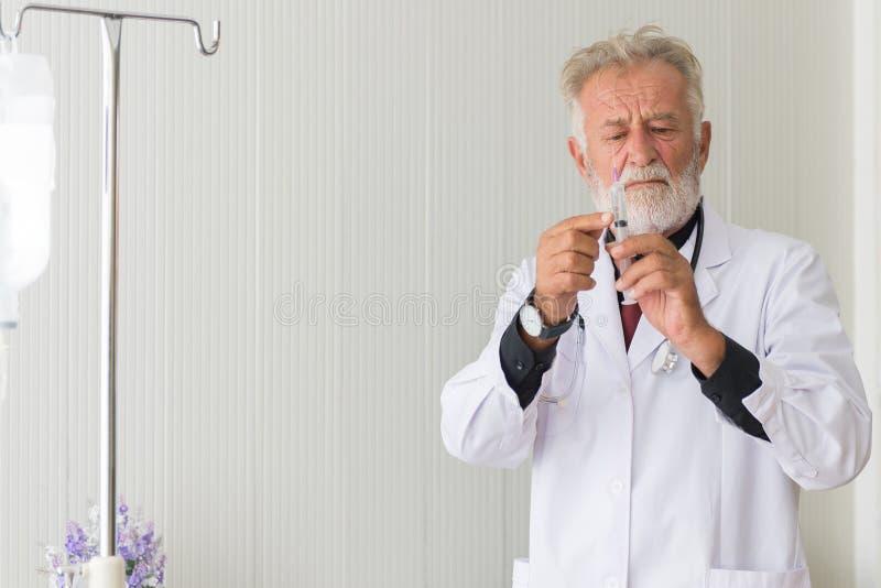 Os homens superiores do doutor preparam a doa??o da vacina com inje??o ou da seringa ao paciente assustado no hospital imagem de stock
