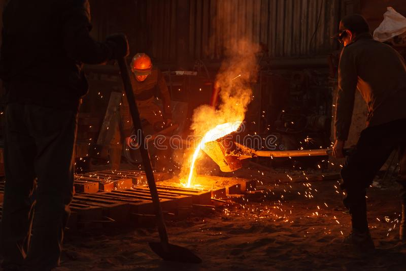 Os homens trabalham com metal quente em uma fábrica de aço fotos de stock royalty free