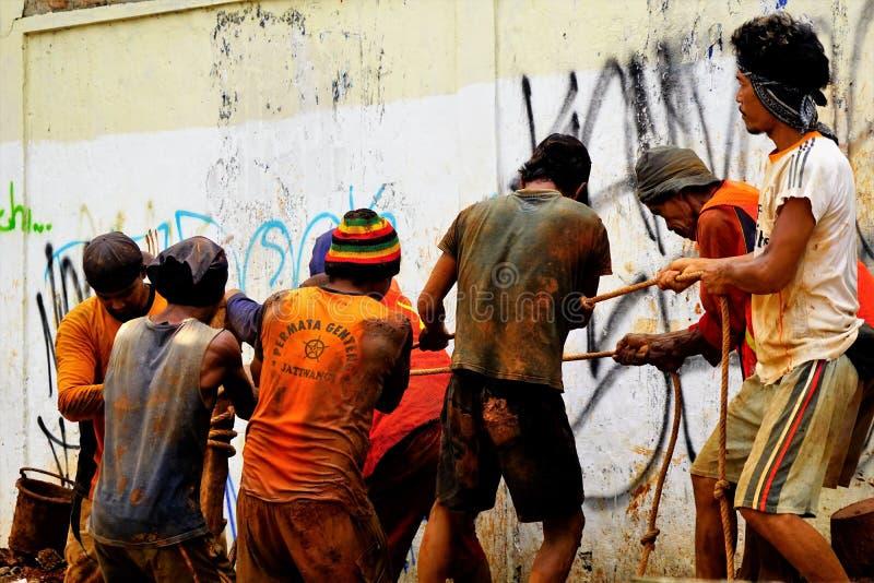 Os homens trabalham em uma equipe para puxar o cabo subterrâneo foto de stock royalty free