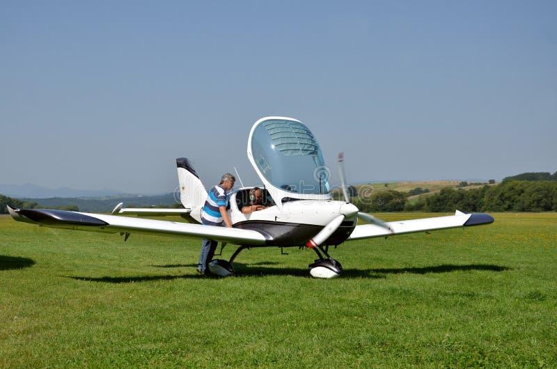 Os homens verificam o avião pessoal pequeno antes de descolar e preparam-se para o voo ao lado da tira de aterrissagem da grama imagem de stock