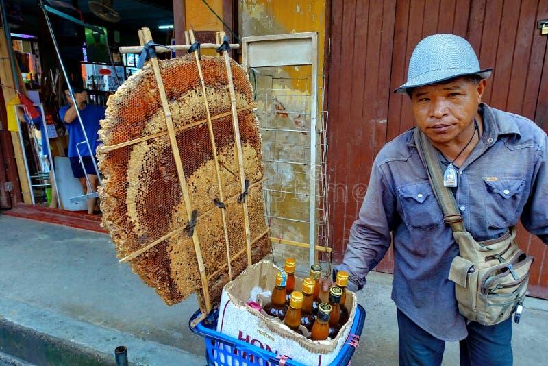 Os homens vestem o chapéu, a camisa no estacionamento azul da bicicleta de brim e mel e favo de mel engarrafados para a venda aos fotos de stock