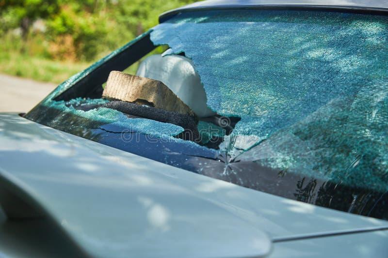 Os hooligan jogaram um tijolo na máquina e quebraram o vidro fotos de stock