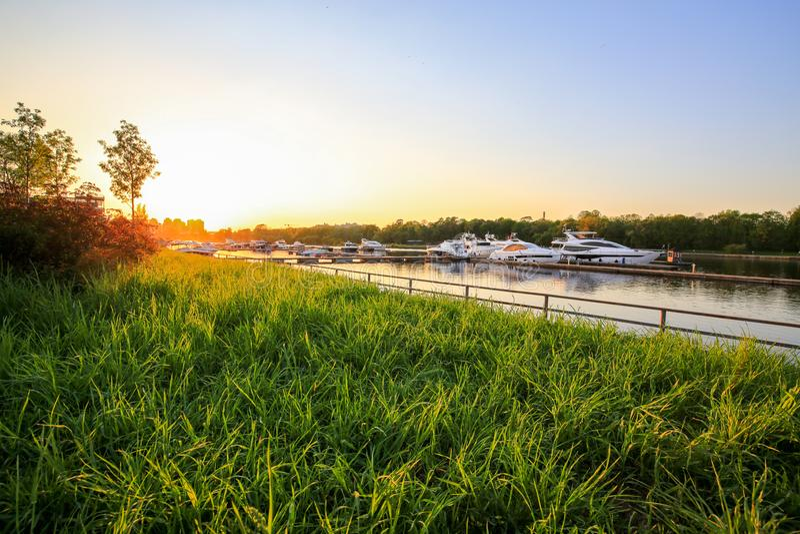 Os iate luxuosos entraram no porto no por do sol colorido Barcos modernos que estacionam no cais Opinião do verão do banco de rio foto de stock