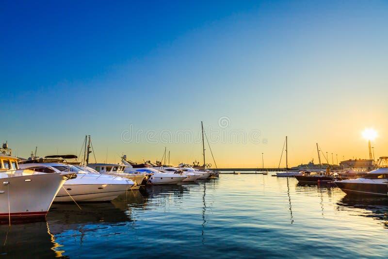 Os iate luxuosos, a navigação e os barcos de motor entraram no porto marítimo no por do sol Estacionamento marinho de barcos a mo foto de stock
