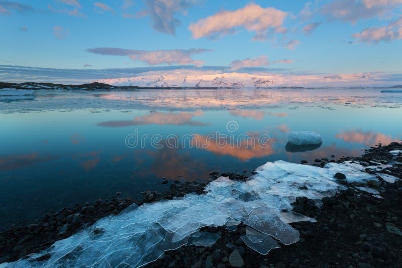 Os iceberg flutuam na lagoa da geleira de Jokulsarlon no nascer do sol, com os picos de montanha do fundo iluminados pelo nascer  fotos de stock