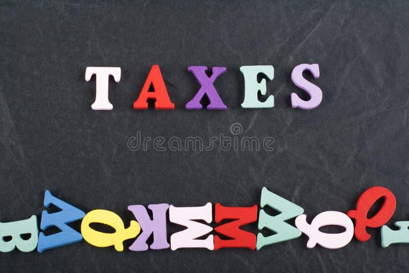 Os IMPOSTOS exprimem no fundo preto da placa composto das letras de madeira do bloco colorido do alfabeto do ABC, copiam o espaço fotografia de stock royalty free