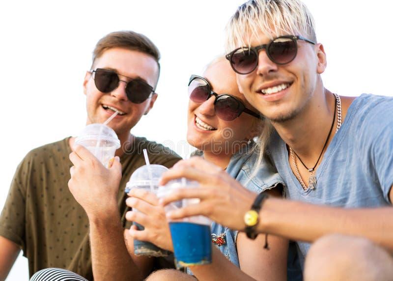 Os indivíduos da forma estão descansando na praia com os cocktail nos sunglass fotografia de stock