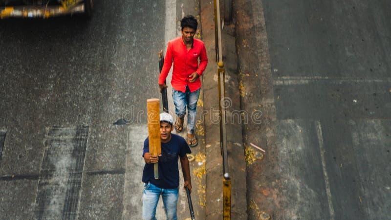 Os indivíduos de Youn cruzam a rua em Bombaim com uma batida do grilo imagem de stock