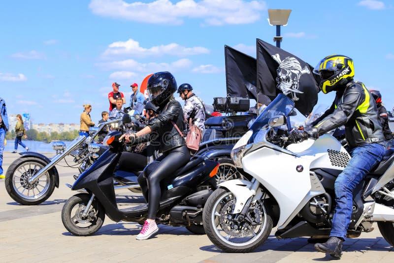Os indiv?duos e as meninas em motocicletas caras bonitas abrem a esta??o da motocicleta Os motociclistas nos capacetes montam em  fotografia de stock
