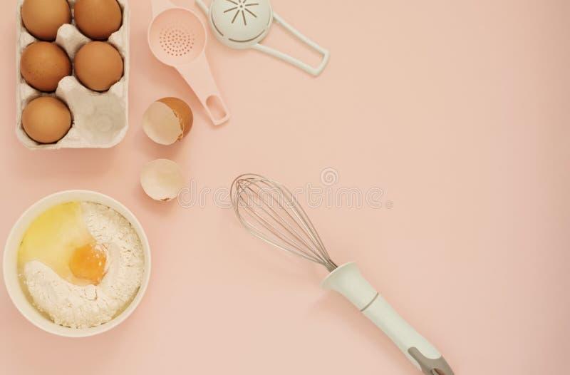 Os ingredientes e a cozinha cozem ferramentas para cozinhar o bolo ou os doces - os ovos, flour, batem em um fundo cor-de-rosa pu fotografia de stock