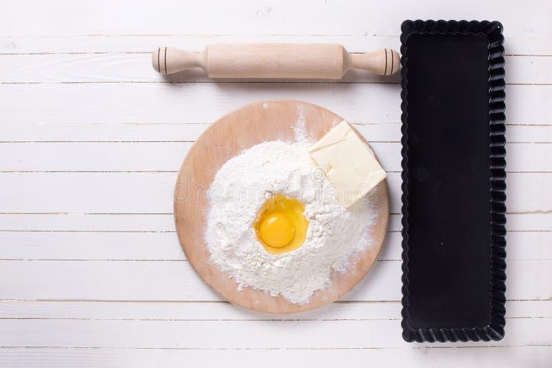 Os ingredientes para a massa flour na placa de madeira, ovo, manteiga imagem de stock royalty free