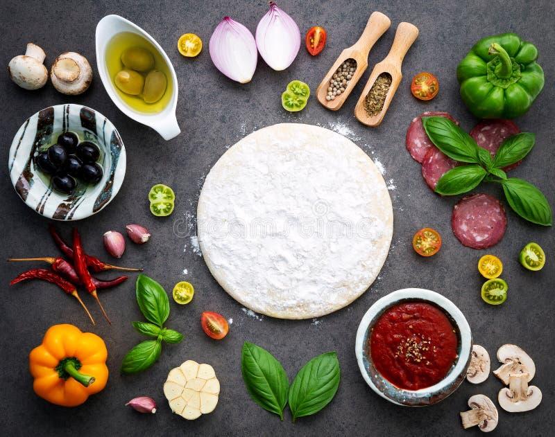 Os ingredientes para a pizza caseiro no fundo escuro fotos de stock