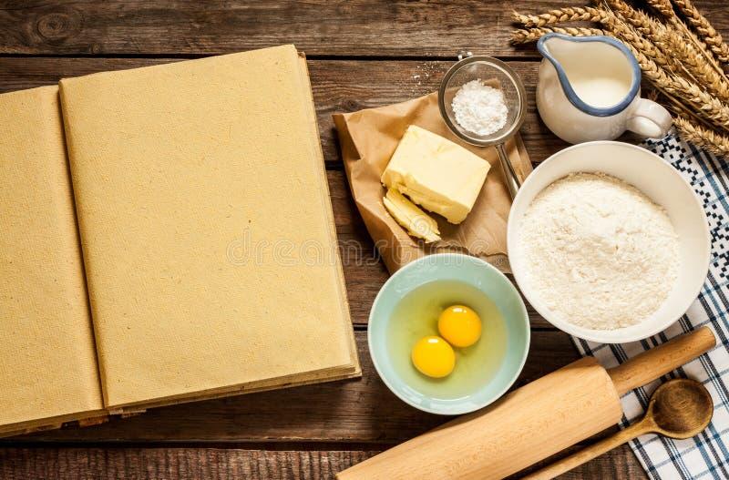 Os ingredientes rurais do bolo do cozimento da cozinha e o cozinheiro vazio registram fotos de stock royalty free