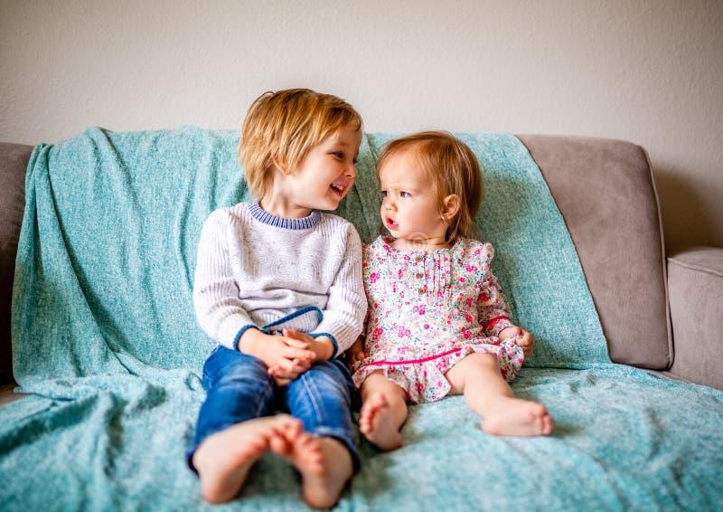 Os irmãos adoráveis sentam-se no sofá junto fotografia de stock royalty free