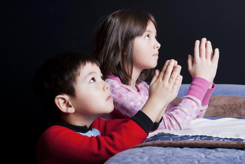 Os irmãos dizem orações das horas de dormir. fotos de stock royalty free