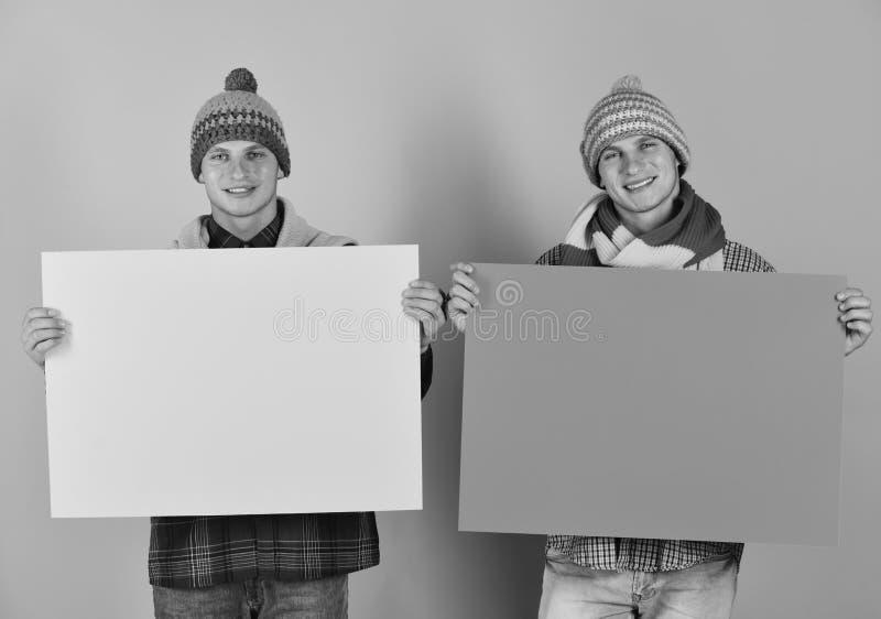 Os irmãos gêmeos em chapéus e em scarves mornos guardam amarelo e as placas alaranjadas, copiam o espaço Venda atual do outono do foto de stock