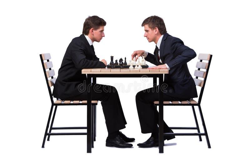 Os irmãos gêmeos que jogam a xadrez isolada no branco imagem de stock