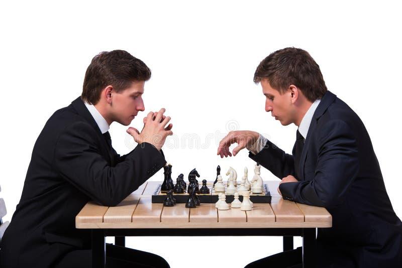 Os irmãos gêmeos que jogam a xadrez isolada no branco imagens de stock