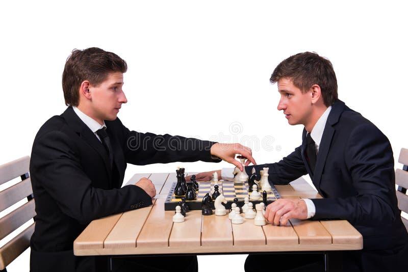 Os irmãos gêmeos que jogam a xadrez no branco foto de stock royalty free