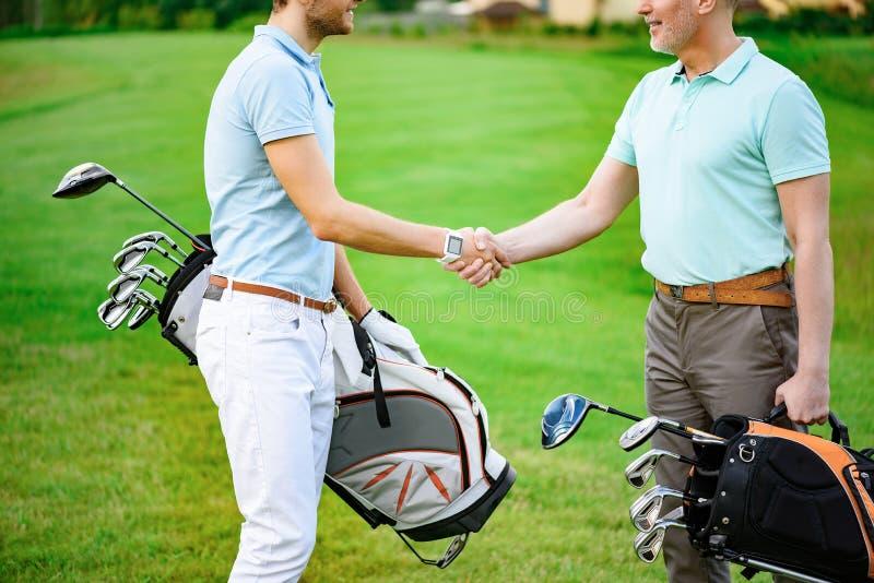 Os jogadores de golfe agitam as mãos um com o otro foto de stock royalty free