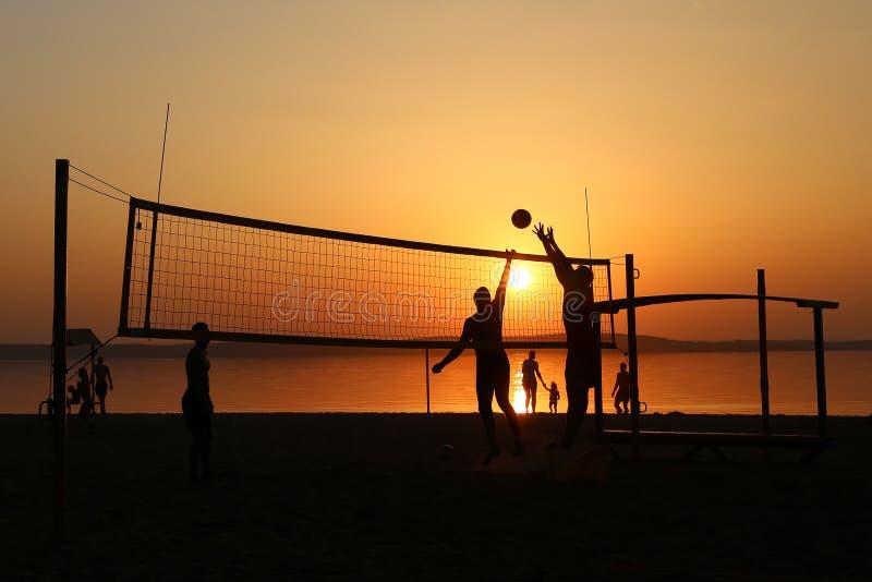 Os jogadores de voleibol saltam durante um fósforo na praia fotos de stock royalty free